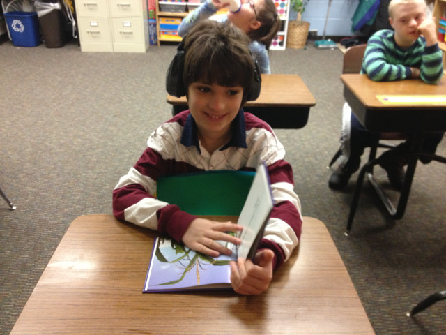 The student is using weighted belts / noise blocking headphones to help him keep his body calm and focused.