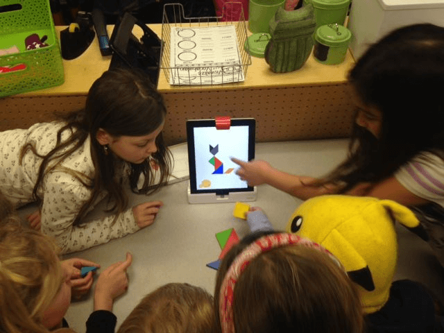 Josie (left) and Right Briley working with a small group, discussing which shapes should go where on the table to create the image on the screen.